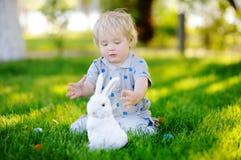 Caza del niño pequeño para el huevo de Pascua en jardín de la primavera el día de Pascua Imagenes de archivo