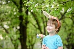 Caza del niño pequeño para el huevo de Pascua en jardín de la primavera el día lindo Fotografía de archivo