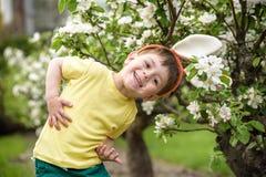 Caza del niño pequeño para el huevo de Pascua en jardín de la primavera el día lindo Imagenes de archivo