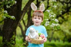 Caza del niño pequeño para el huevo de Pascua en jardín de la primavera el día lindo Fotos de archivo libres de regalías