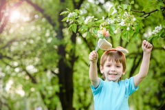 Caza del niño pequeño para el huevo de Pascua en jardín de la primavera el día lindo Foto de archivo