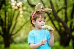 Caza del niño pequeño para el huevo de Pascua en jardín de la primavera el día lindo Imágenes de archivo libres de regalías