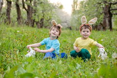 Caza del niño pequeño para el huevo de Pascua en jardín de la primavera el día lindo Imagen de archivo libre de regalías