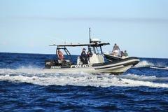 Caza del oficial de policía en el barco de la gasolina Imagenes de archivo