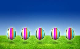 Caza rayada púrpura del huevo de cinco Pascua en hierba Foto de archivo