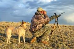 Cazador camuflado con el rifle y el perro del seguimiento Fotos de archivo