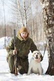 Cazador con el labrador retriever y la escopeta en bosque del invierno Fotografía de archivo