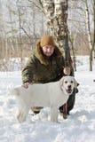 Cazador con el labrador retriever y la escopeta en bosque del invierno Imágenes de archivo libres de regalías