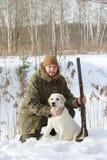 Cazador con el labrador retriever y la escopeta en bosque del invierno Imagenes de archivo