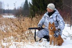 Cazador con el perro en campo nevoso fotos de archivo