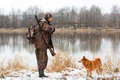 Cazador con el perro en el riverbank imagen de archivo libre de regalías