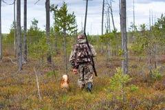 Cazador con el perro que camina en el bosque del pino de pantano fotografía de archivo