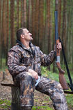 Cazador con la escopeta en el campo del bosque imagen de archivo