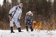 Cazador con su hijo en la caza del invierno Foto de archivo libre de regalías