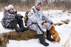 Cazador con su hijo y perro durante el resto Fotos de archivo