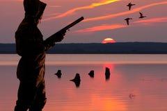 Cazador con una escopeta en la búsqueda de las aves acuáticas fotografía de archivo libre de regalías