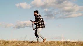 Cazador con una escopeta en una ropa del tiroteo del vintage Cazador del hombre con un arma Búsqueda de período Un cazador con un metrajes