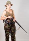 Cazador de la muchacha en el camuflaje, cargas del arma Fondo gris Imagen de archivo