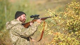 Cazador del hombre con el arma del rifle Boot Camp Habilidades de la caza y equipo del arma C?mo caza de la vuelta en la afici?n  imágenes de archivo libres de regalías