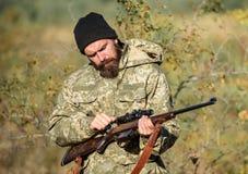 Cazador del hombre con el arma del rifle Boot Camp Moda del uniforme militar Cazador barbudo del hombre Fuerzas del ejército camu imagen de archivo libre de regalías