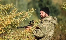 Cazador del hombre con el arma del rifle Boot Camp Moda del uniforme militar Cazador barbudo del hombre Fuerzas del ejército camu imagen de archivo