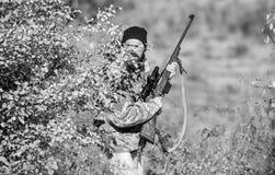 Cazador del hombre con el arma del rifle Boot Camp Moda del uniforme militar Cazador barbudo del hombre Fuerzas del ej?rcito camu imagen de archivo