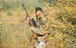 Cazador del hombre con el arma del rifle Boot Camp Moda del uniforme militar Cazador barbudo del hombre Fuerzas del ej?rcito camu foto de archivo