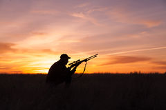 Cazador del rifle en la puesta del sol Fotos de archivo