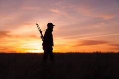 Cazador del rifle en puesta del sol Fotografía de archivo