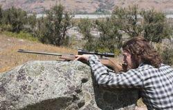 Cazador que mira a través del rifle del alcance Fotos de archivo