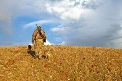 Cazador y perros camuflados en paisaje de la salida del sol Imagen de archivo