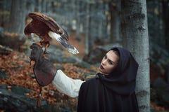 Cazadora hermosa con el halcón en un bosque Fotos de archivo libres de regalías