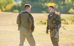 Cazadores del hombre con el arma del rifle Boot Camp Amistad de los cazadores de los hombres Fuerzas del ej?rcito camuflaje Moda  imagen de archivo libre de regalías