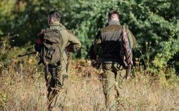 Cazadores del hombre con el arma del rifle Boot Camp Uniforme militar Amistad de los cazadores de los hombres Fuerzas del ejércit foto de archivo