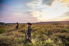 Cazadores que eligen la buena posición para la caza del pato en campo rural durante salida del sol hermosa Foto de archivo libre de regalías