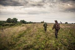 Cazadores que pasan a través de campo rural con el cielo dramático durante temporada de caza Fotografía de archivo libre de regalías