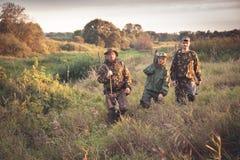 Cazadores que pasan a través de garass altos en campo rural en el amanecer durante temporada de caza Imagen de archivo libre de regalías