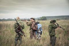 Cazadores que se preparan para cazar en campo rural en día cubierto durante temporada de caza Fotografía de archivo