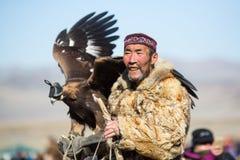 Cazaque Eagle Hunter dourado na roupa tradicional, com uma águia dourada em seu braço Imagem de Stock