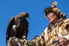 Cazaque Eagle Hunter dourado na roupa tradicional, com uma águia dourada em seu braço Imagens de Stock Royalty Free
