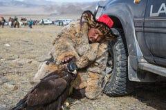 Cazaque Eagle Hunter dourado na roupa tradicional, com uma águia dourada em seu braço Foto de Stock