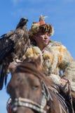 Cazaque Eagle Hunter dourado na roupa tradicional, com uma águia dourada em seu braço Fotografia de Stock