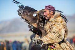 Cazaque Eagle Hunter dourado na roupa tradicional, com uma águia dourada em seu braço durante a competição nacional anual com pás Foto de Stock Royalty Free