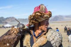 Cazaque Eagle Hunter dourado na roupa tradicional, com uma águia dourada em seu braço durante a competição nacional anual com pás Imagem de Stock Royalty Free