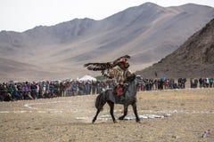 Cazaque Eagle Hunter dourado na roupa tradicional, com uma águia dourada em seu braço durante a competição nacional anual com pás Fotografia de Stock
