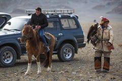 Cazaque Eagle Hunter dourado na roupa tradicional, com uma águia dourada em seu braço durante a competição nacional anual com pás Foto de Stock