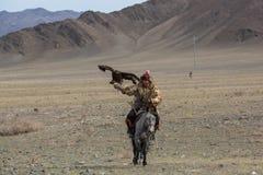 Cazaque Eagle Hunter dourado na roupa tradicional, com uma águia dourada em seu braço durante a competição nacional anual Foto de Stock