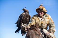 Cazaque Eagle Hunter dourado na roupa tradicional, com uma águia dourada em seu braço durante a competição nacional anual com pás Fotos de Stock Royalty Free