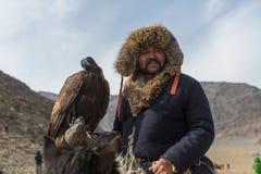 Cazaque Eagle Hunter dourado na roupa tradicional, durante a competição nacional anual com os pássaros do ` de Berkutchi do ` da  Fotos de Stock Royalty Free