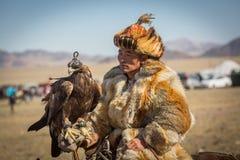 Cazaque Eagle Hunter dourado na roupa tradicional, durante a competição nacional anual com os pássaros do ` de Berkutchi do ` da  Imagens de Stock